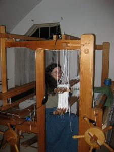 Bringing the warp through the heddles.